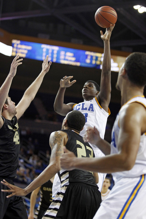 Description of . UCLA center Tony Parker shoots over Oakland forward Corey Petros, left, and forward Tommie McCune (23) in the second half of their NCAA college basketball game Tuesday, Nov. 12, 2013, in Los Angeles. UCLA won the game 91-60.  (AP Photo/Alex Gallardo)
