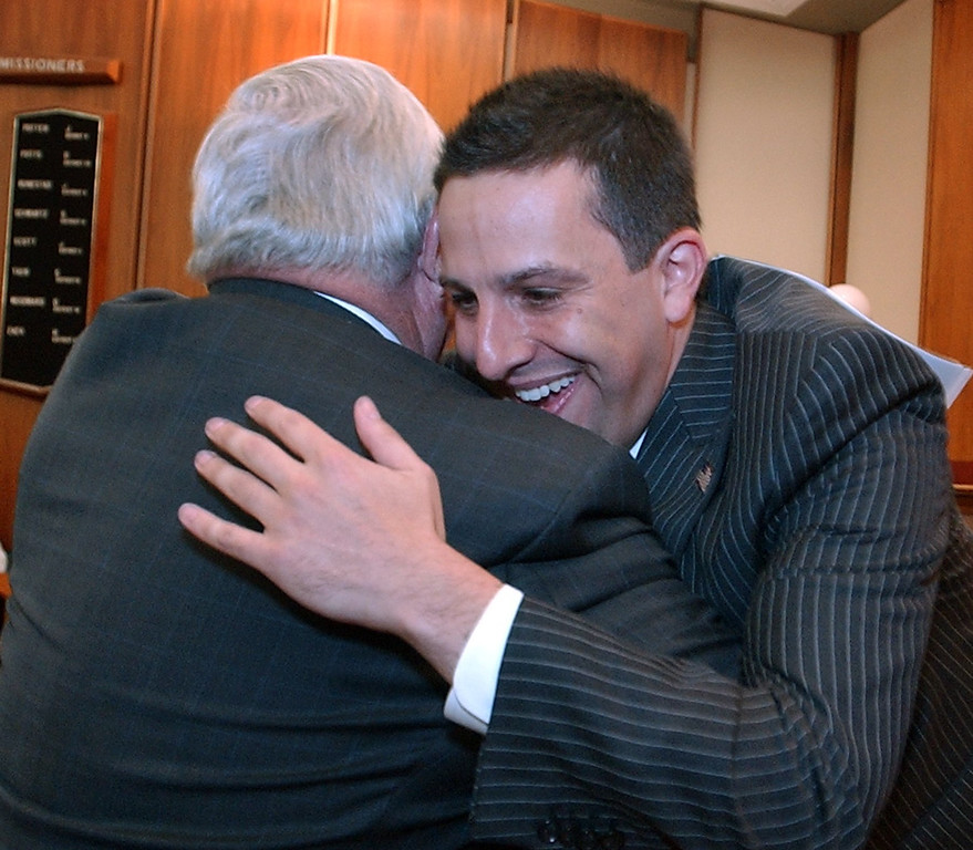 Description of . (right) Andy Meisner gets a hug from Oakland County Executive L. Brooks Patterson after his remarks leading up to the swearing in of Meisner as Oakland County Treasures at the Board of Commissioners Auditorium.