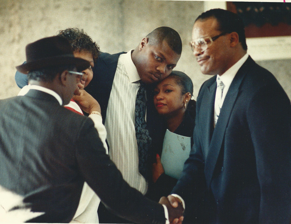 Description of . Former Lions player Reggie Rogers (center) with family and attorney Elbert Hatchett (right) outside a courtroom in Oakland County Circuit Court in December 1989. Oakland Press file photo