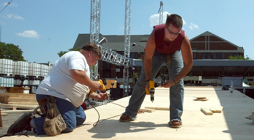 Description of . Fritz Seelmann,left, of Harriston Twp. along with partner Bo Marasco of Chesterfield Twp. co-owners of CBSM & Associates work on the main ramp to the stage area for the Ford Exhibit located near Shane Park in downtown Birmingham for this weekends Dream Cruise.