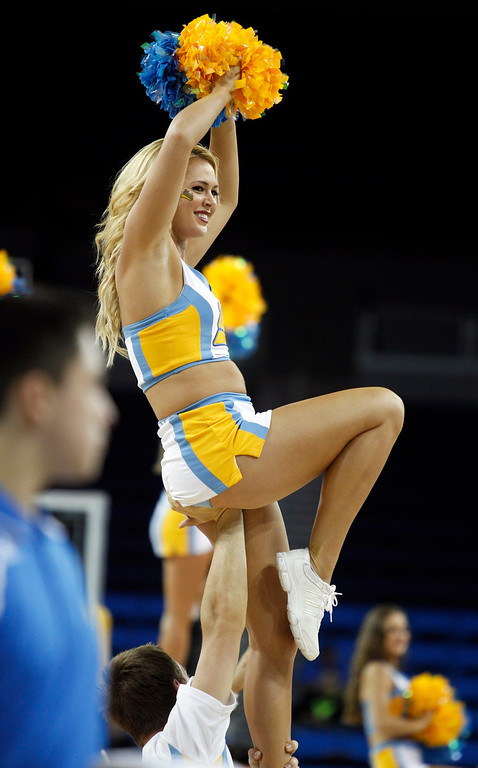 Description of . UCLA cheerleader during a timeout in the second half of their NCAA college basketball game against Oakland Tuesday, Nov. 12, 2013, in Los Angeles. UCLA won the game 91-60.  (AP Photo/Alex Gallardo)