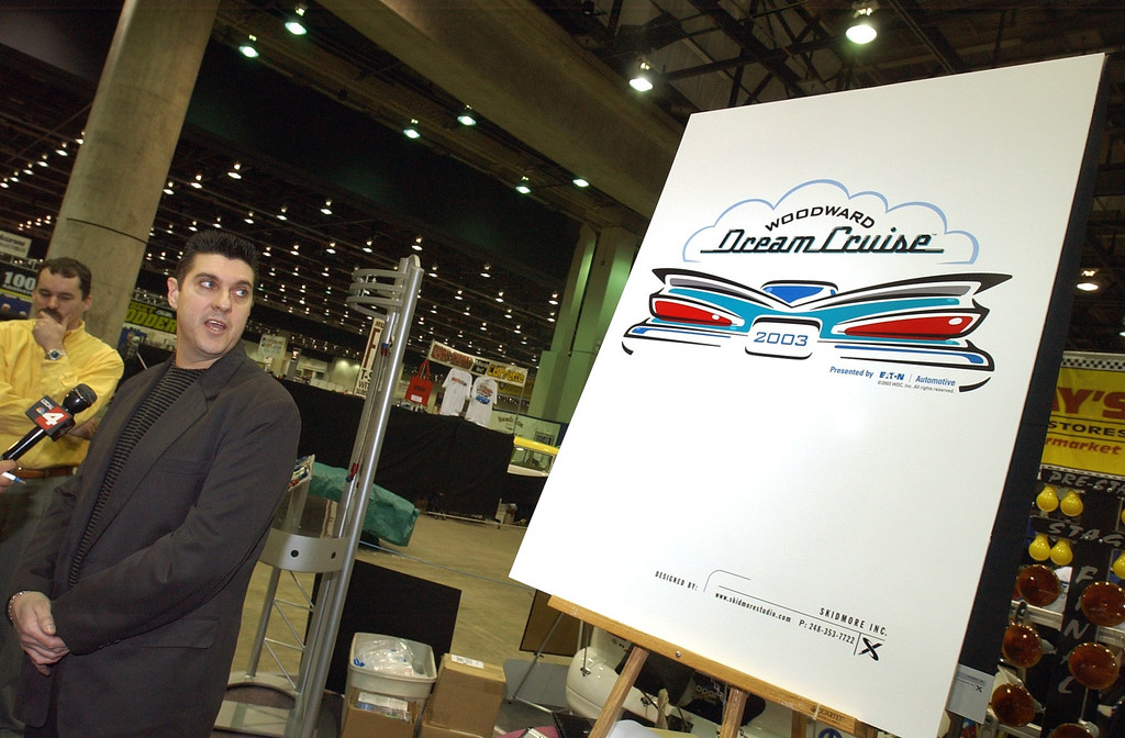 . Joe Borri of Skidmore Inc. describes the new Dream Cruise logo, Friday, February 21, 2003, at Autorama held at the Cobo Center in Detroit, Mich.  Standing behind him is Tim Smith, VP/Marketing Director for Skidmore Inc.