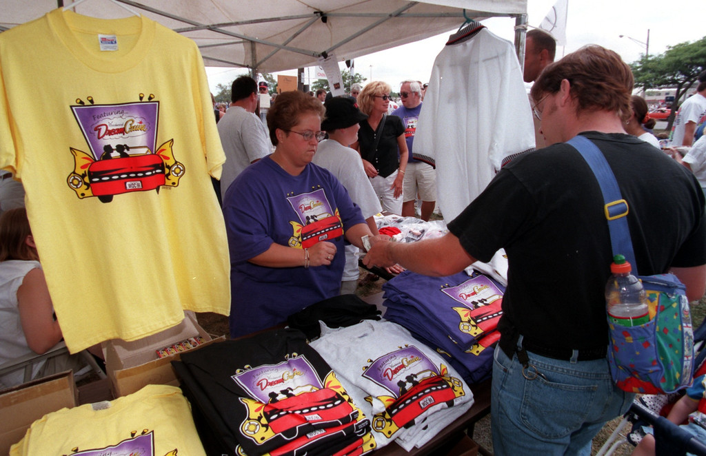 Description of . Patti Moyer, left, sells Woodward Dream Cruise T-Shirts with the money going twords the Boy\'s & Girls Club during the Fifth Annual Woodward Dream Cruise.