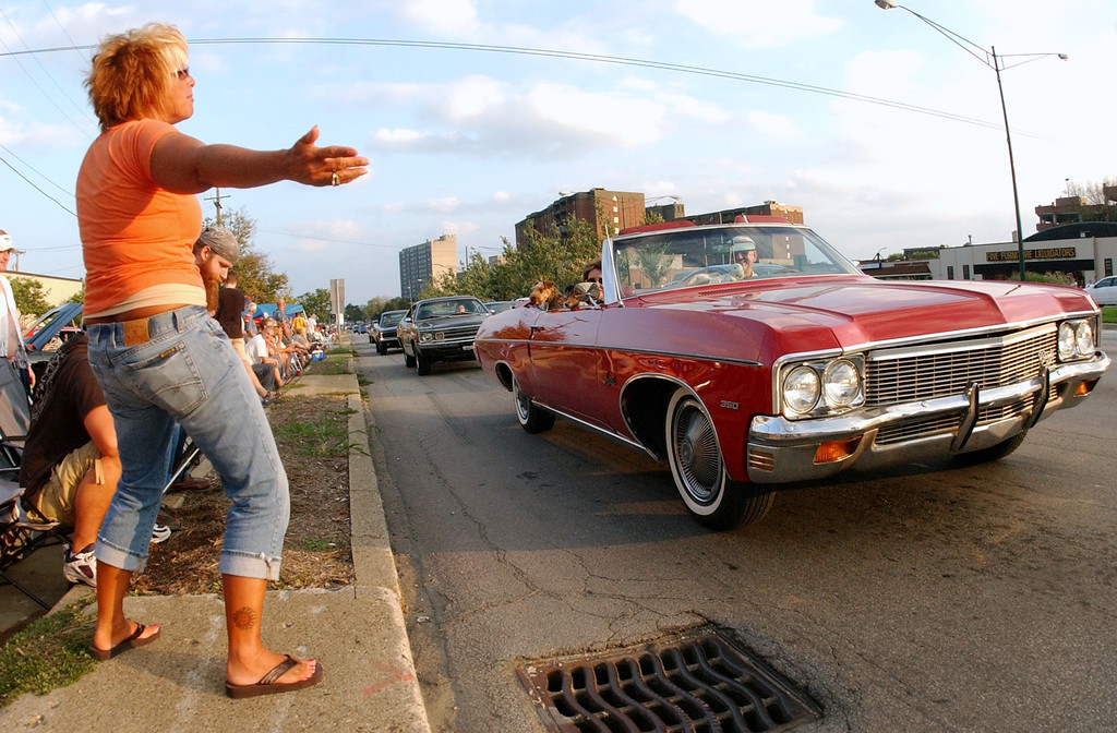 . Bonnie Milligan, left, of Columbus, Ohio, tried without success to get this motorist to burn his wheels, Friday, August 19, 2005, near the corner of Maple and Woodward in Birmingham, Mich.
