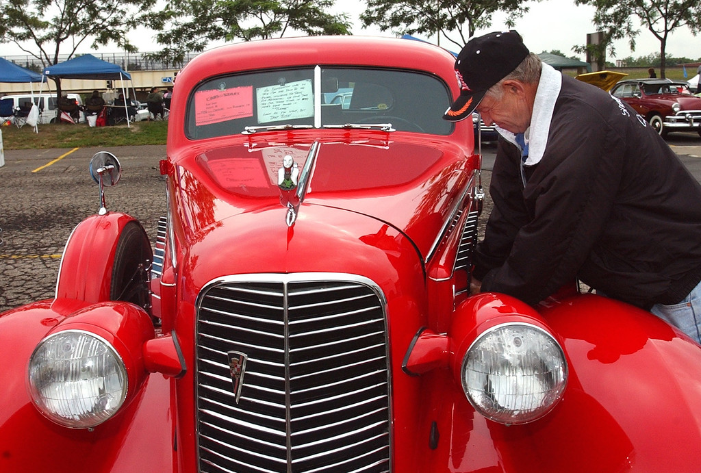 Description of . Fred Swan of Oxford closes the hood to his 1936 Cadillac car on display in the parking lot of the Phoneix Plaza in downtown Pontiac during Friday night\'s Woodward Dream Cruise. The annual classic cruise goes from Pontiac to Ferndale covering 16-miles of classic cars, food & entertainment along the way.