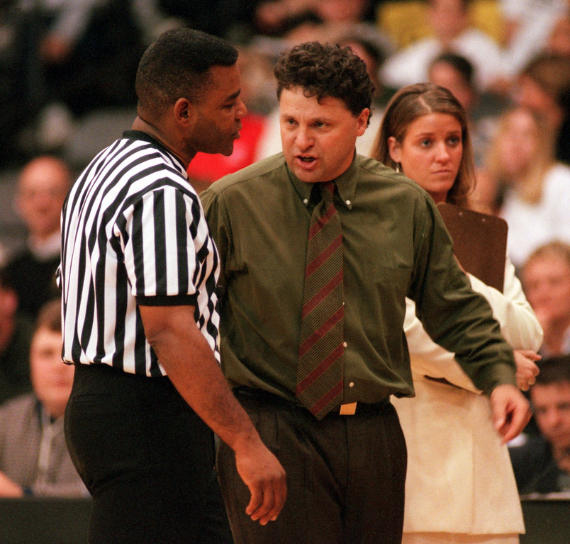 Description of . Oakland University mens' basketball head coach Greg Kampe (middle) talks to an unidentified official about a foul call against his team, during second half action against Illinois State University, Sunday, November 21, 1999.  Standing in back right is assistant coach Jennifer Johnston.
