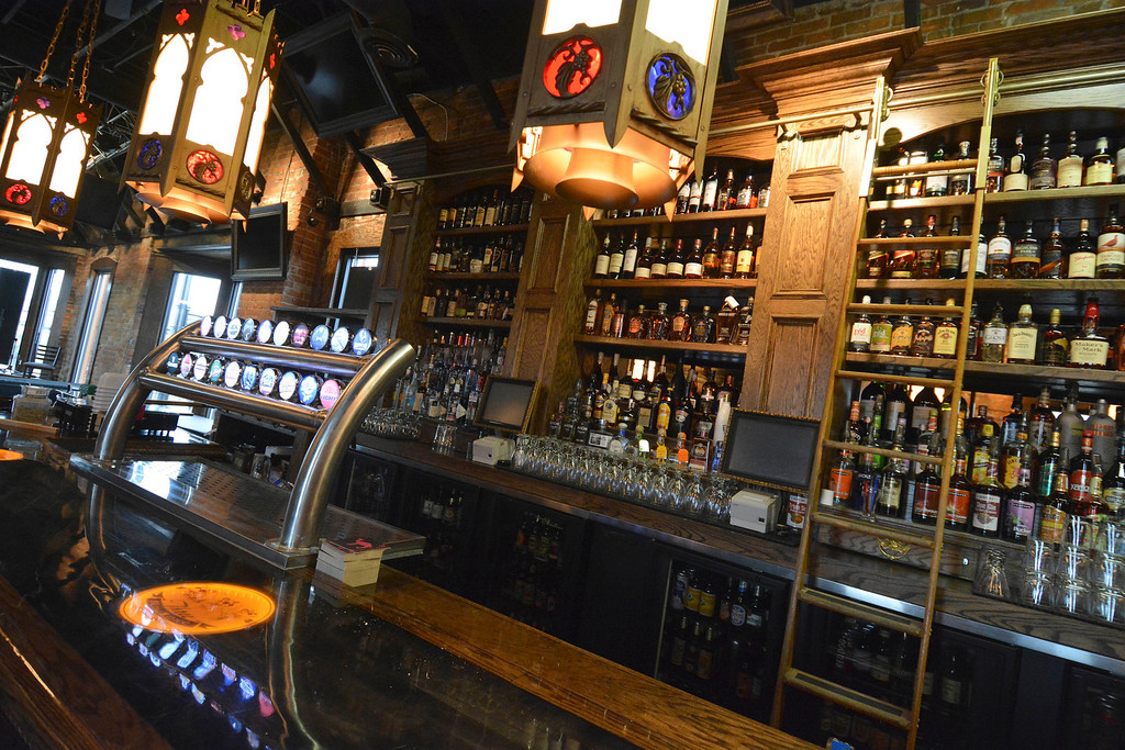 Description of . The upstairs bar at Three Blind Mice in Mount Clemens has the same wood and brass trim, with cathedral lamps overhead. Ray J. Skowronek/Digital First Media