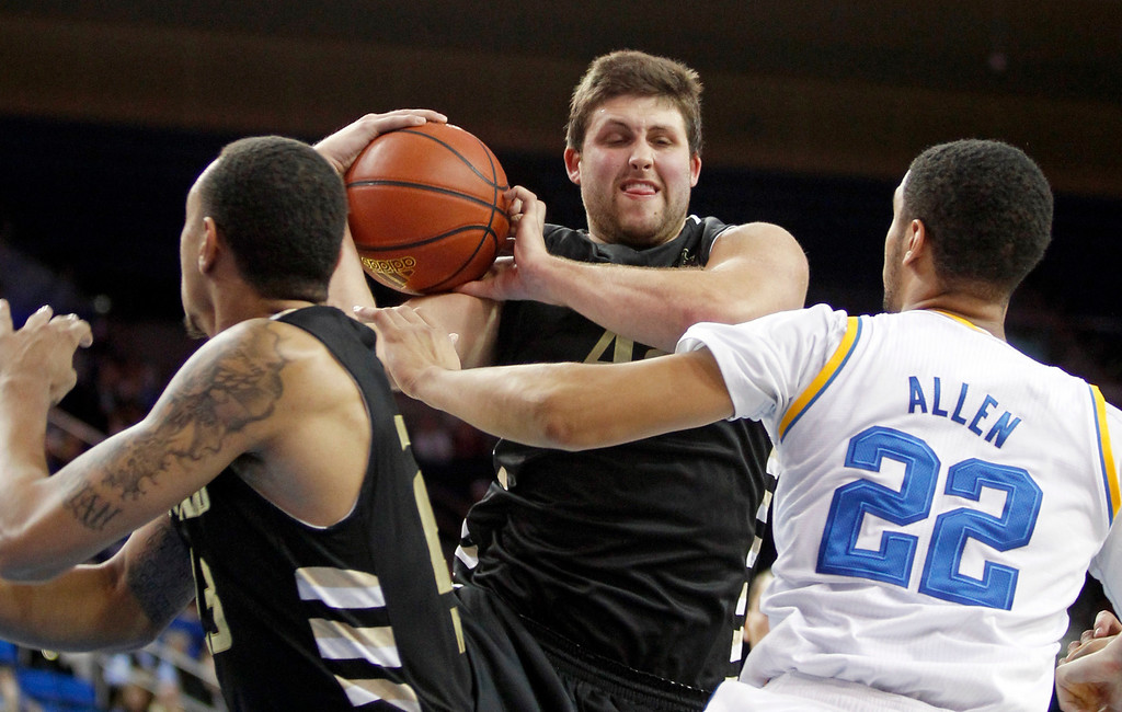 Description of . Oakland center Corey Petros, center, pulls down a rebound between teammate Tommie McCune, left, and UCLA guard Noah Allen (22) in the second half of an NCAA college basketball game Tuesday, Nov. 12, 2013, in Los Angeles. UCLA won 91-60.  (AP Photo/Alex Gallardo)
