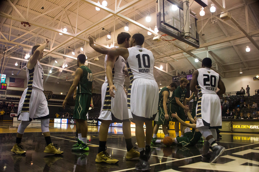 Description of . Golden Grizzlies players celebrate Duke Mondy's layup early in the first quarter, as players from Tiffin help their teammate off the floor. Photo by Dylan Dulberg