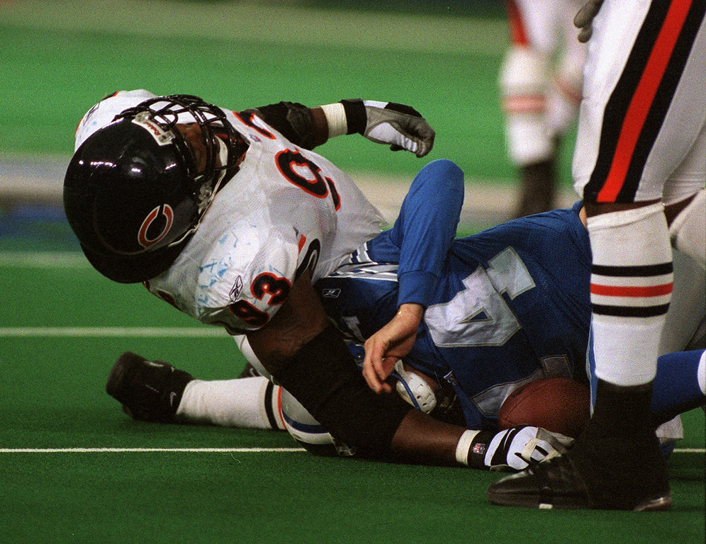 . Chicago Bears defensive end Phillip Daniels (top) smashes Detroit Lions quarterback Ty Detmer into the turf after a hard sack during the Lions\' 24-0 loss at the Pontiac Silverdome Sunday. The Lions are 1-14.  Daniels was momentarily injured on the play.