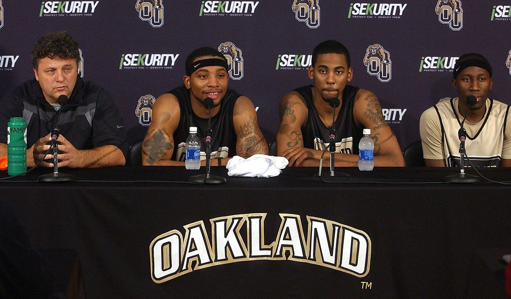 Description of . (from left) Greg Kampe, Oakland University men's basketball head coach, talks to the press as players Derick Nelson, Keith Benson and Johnathon Jones listen during Media Day at the O'Rena.