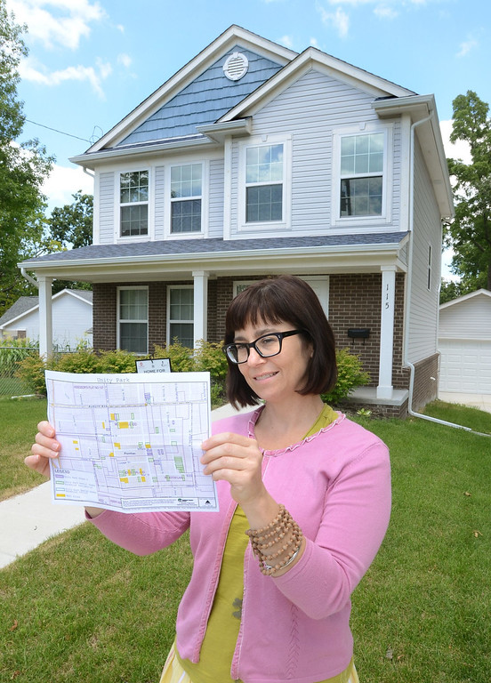 Description of . Kristen Elliott, vice president of Development for the Community Housing Network, with a site plan, in front of the type of house that will be built for a 32-unit rental home development in Unity Park in Pontiac.  Thursday, July 25, 2013.  The Oakland Press/TIM THOMPSON