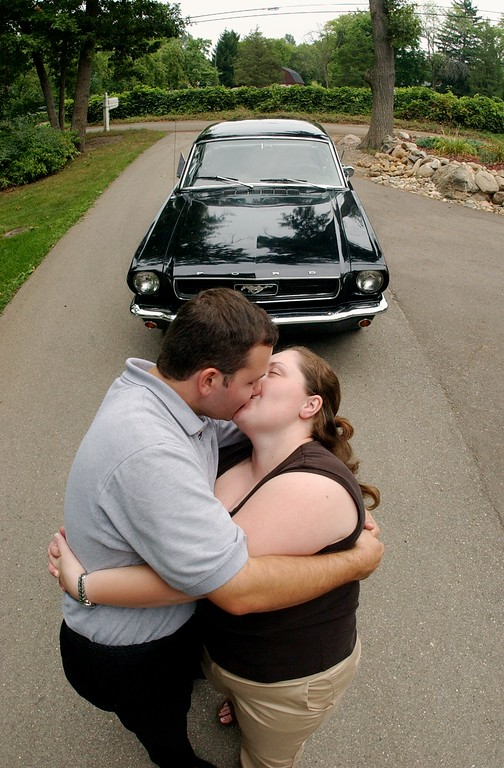 Description of . Bryan Crandall, left, kisses his fiance, Michelle Barnett, in front of his father's 1966 Mustang, which they will drive after their wedding on Saturday, along the Dream Cruise route.  Photo taken on Thursday, August 18, 2005, in Waterford, Mich.