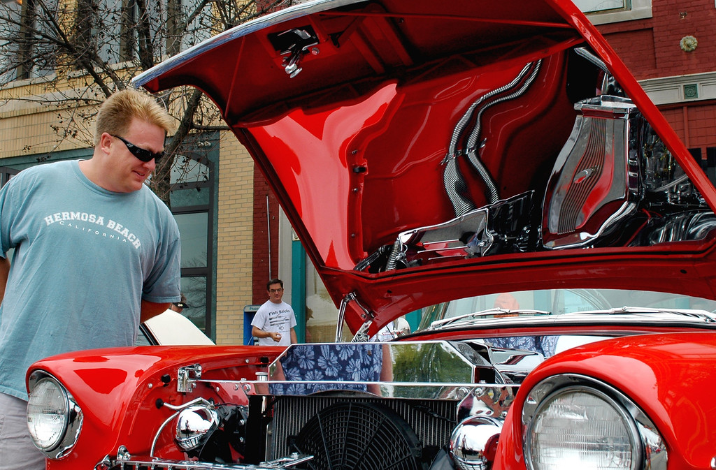 Description of . Bill Slonaker, of Keego Harbor, checks out a 1955 Chevy on the streets of Pontiac Saturday afternoon during the annual Woodward Dream Cruise.