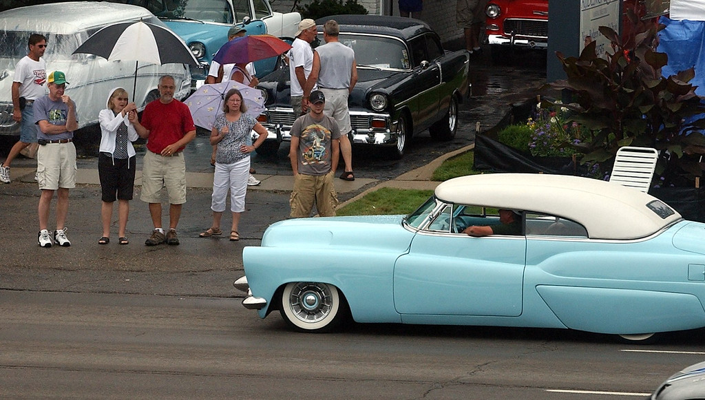 . Onlookers braved the rainy weather to watch some of the classic cars during the 16th Annual Woodward Dream Cruise in Royal Oak. (Oakland Press Photo/Vaughn Gurganian)