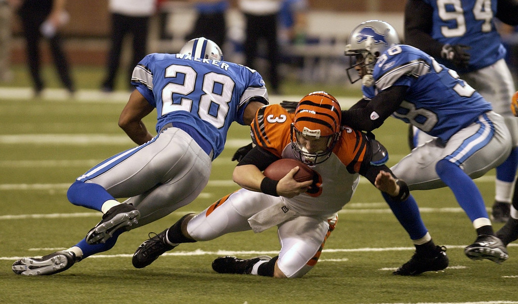 . Detroit Lions\' Bracy Walker (28) and Keith Smith (38) pressure Cinncinati Bengals\' QB Jon Kitna (3) at Ford Field in Detroit. Photographed Sunday, December 18, 2005.