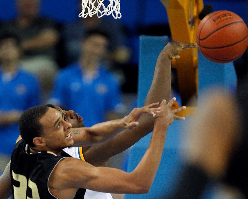 Description of . Oakland forward Tommie McCune, left, battles UCLA center Tony Parker for a rebound in the second half of their NCAA college basketball game Tuesday, Nov. 12, 2013, in Los Angeles. UCLA won the game 91-60.  (AP Photo/Alex Gallardo)