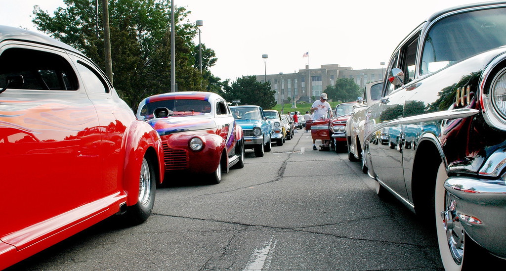 Description of . Lines of cars wait on Water Street in Pontiac Friday morning to be some of the first into the parking lot for the annual Woodward Dream Cruise car show.