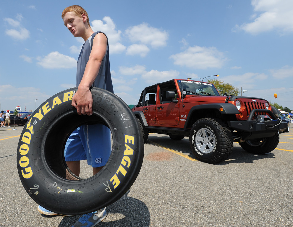 Description of . Michael Lay, age 13, of Royal Oak, Mich., carries his contest giveaway winnings, a used car tire that was once used on a NASCAR race vehicle during one of the NASCAR races.  Lay, who is a NASCAR fan, said he will clean it up and use the tire as a decoration in his room.  His mom consented.  Photo taken during the Woodward Dream Cruise on Saturday, August 15, 2009, in Royal Oak, Mich.  (The Oakland Press/Jose Juarez)