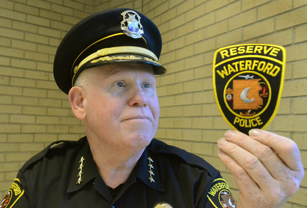 Description of . Waterford Police Chief Dan McCaw with a reserve officer patch.  The department is looking to add up to 15 reserve officers.    Tuesday, July 23, 2013.  The Oakland Press/TIM THOMPSON