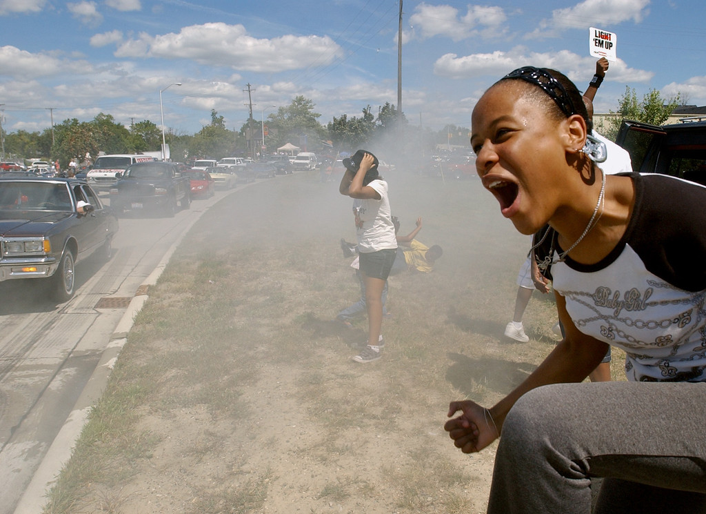Description of . Myesha Griffin, age 16, of Pontiac, Mich., lets out a yell after a vehicle had burned rubber and left smoke in its wake, as other cars follow the loop around downtown Pontiac during the annual Dream Cruise.  Photo taken on Saturday, August 16, 2008, in Pontiac, Mich.  (The Oakland Press/Jose Juarez)