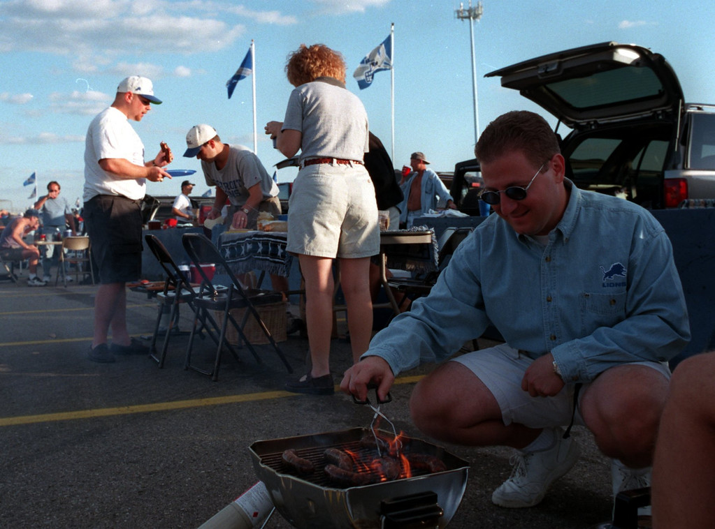 Description of . Phil Fracassa of Gross Pt. grills Italian sausage prior to the start of the Detroit Lions Monday nights game against the Tampa Buccaneers at the Pontiac Silverdome.