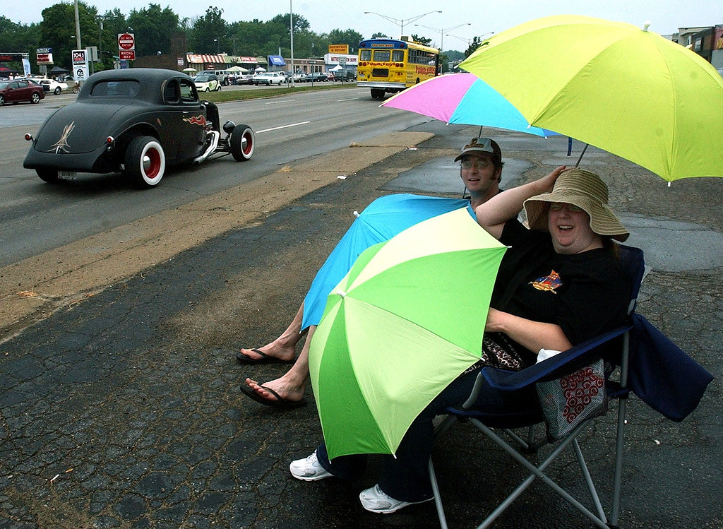 Description of . Steady rain didn't stop John Drolet and Ellen Klausmeyer from enjoying the 16th Annual Woodward Dream Cruise in Royal Oak. (Oakland Press Photo/Vaughn Gurganian)