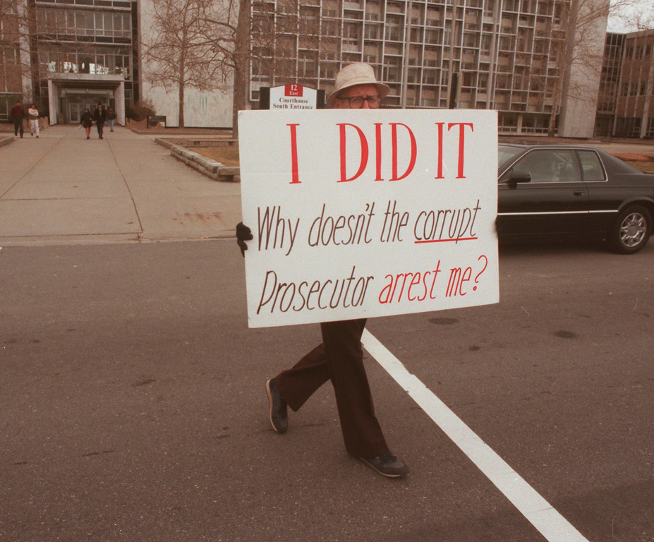 . Dr. Jack Kevorkian leaves the Oakland County Courthouse after picketing with his sign outside of the south entrance.