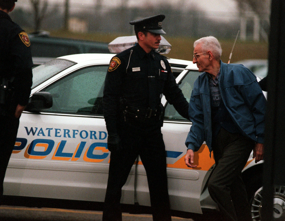 . Jack Kevorkian is escorted to the courthouse in Waterford Township by police officers for his arraignment Wednesday after turning himself in.