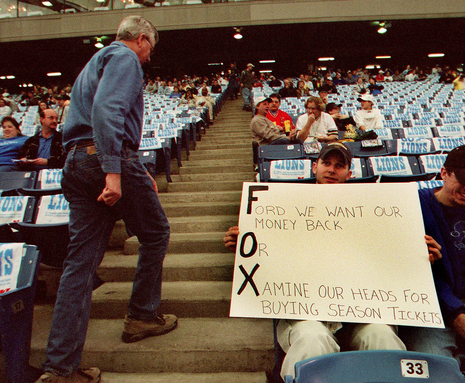 ". A passerby checks out Joseph  Okray\'s sign that reads ""Ford we want our mney back Or Xamine our heads for buying season tickets\"" during the Detroit Lions 29-27 loss to the Green Bay Packers Thursday at the Pontiac Silverdome.  The letters of each part of the sign spell out FOX, it was Okray\'s attempt to get his face on TV."