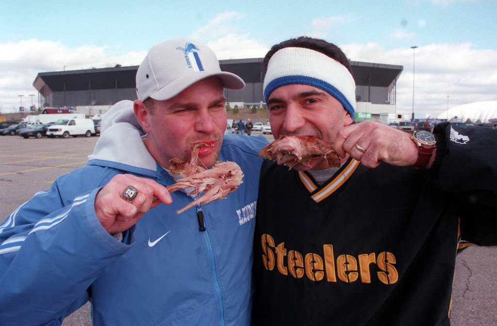 . Rival fans, Jamie Little of Waterford and Jeff Massey of Cleveland, share some turkey before the Lions-Steelers game at the Pontiac Silverdome.  The Lions won the game 19-16 in overtime.