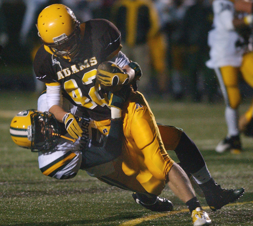 . Rochester Adams High School football player Alec Prechtel, front, runs for yardage and is tackled by Farmington Hills Harrison defender David Evans during first quarter action, Friday, October 9, 2009, at Adams HS in Rochester Hills, Mich.  (The Oakland Press/Jose Juarez)