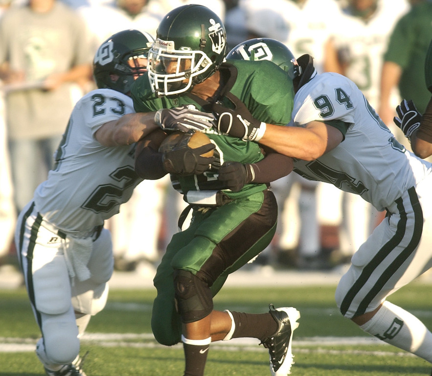 . West Bloomfield High School football player Cameron Fields, middle, is tackled by Lake Orion defenders Dillon Siterlet, far left, and Kane Hayes during first quarter action, Thursday, September 3, 2009, in a game played at West Bloomfield HS in West Bloomfield, Mich.  (The Oakland Press/Jose Juarez)