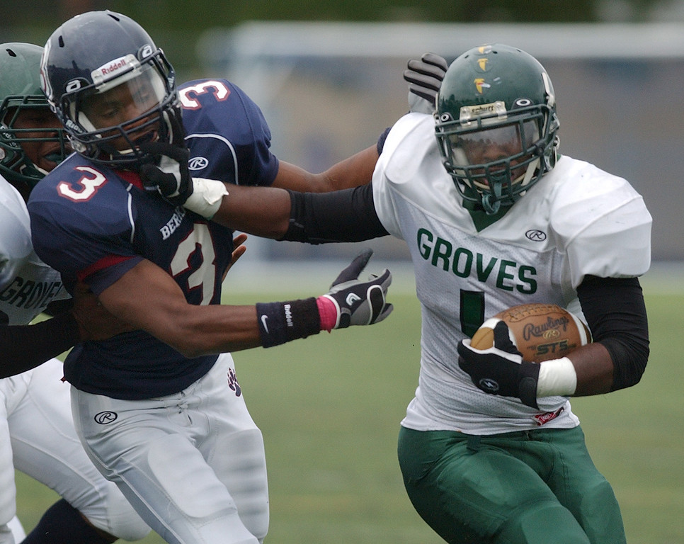 . Birmingham Groves High School football player Jalen Spicer, right, runs for yardage as he pushes off Berkley defender Eric Hudson during first quarter action.  Photo taken on Saturday, September 11, 2010, in a game played at Hurley Field in Berkley, Mich.  (The Oakland Press/Jose Juarez)