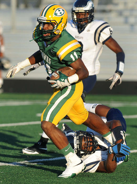 . Farmington Hills Harrison High School football player Gairus Coleman runs past the tackle of an unidentified Southfield defender during first quarter action.  Photo taken on Friday, September 3, 2010, in a game played at Harrison HS in Farmington Hills, Mich.  (The Oakland Press/Jose Juarez)
