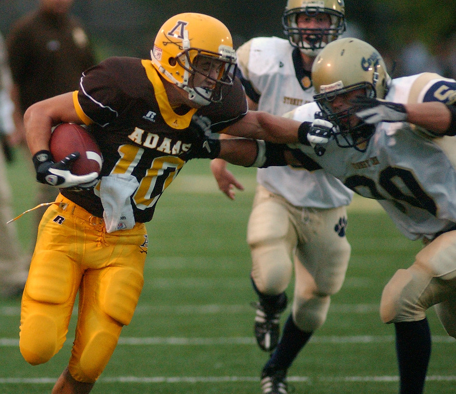 . Rochester Adams High School football player Cody Wilson, left, runs for yardage against Stoney Creek in the first quarter, Friday, September 5, 2008, in a game played at Adams HS in Rochester Hills, Mich.  (The Oakland Press/Jose Juarez)