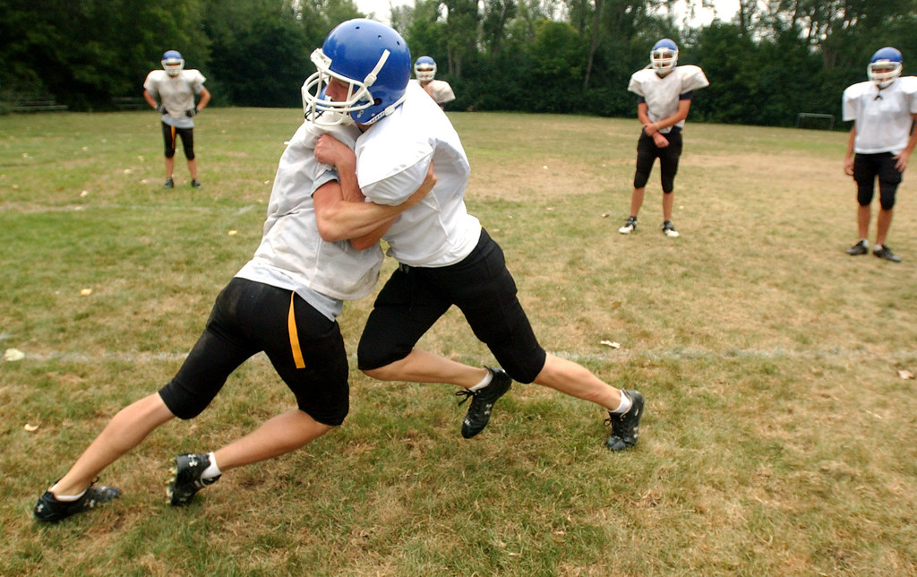 ". Southfield Christian High School football players Justin Basler, left, and Bryan Brownlee work on their tackling skills during a drill called ""Bull in the Ring.\""  Photographed during practice held at Southfield Christian HS in Southfield, Mich., Monday, August 14, 2006.  (The Oakland Press/Jose Juarez)"