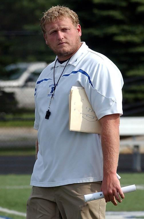 . Erik Vernon, Rochester High School football coach, watches his team practice. (Oakland Press Photo/Vaughn Gurganian)