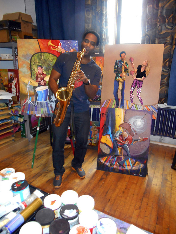 . Southfield artist Marcus Glenn plays around in his studio in Corktown, Detroit. The characters in the picture right of him represent Marcus and his wife, Yolanda, with maracas. Photo by Nicole M. Robertson
