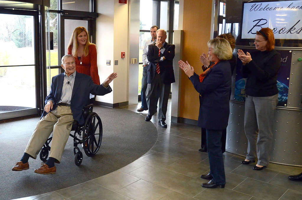 . Oakland County Executive L. Brooks Patterson waves to well-wishers while being pushed in his wheelchair by his daughter Mary moments before meeting the media on his first day back at work, Tuesday October 30, 2012.  (Oakland Press Photo By: Vaughn Gurganian)