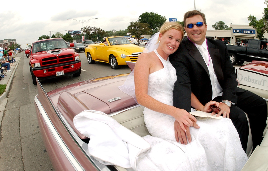 . Just married couple Courtney and Chris Mikoliczeak of Berkley, Mich., spend part of their wedding day riding along the route of the Dream Cruise.  Their wedding took place in Birmingham.  Photo taken on Saturay, August 20, 2005, in Royal Oak, Mich.