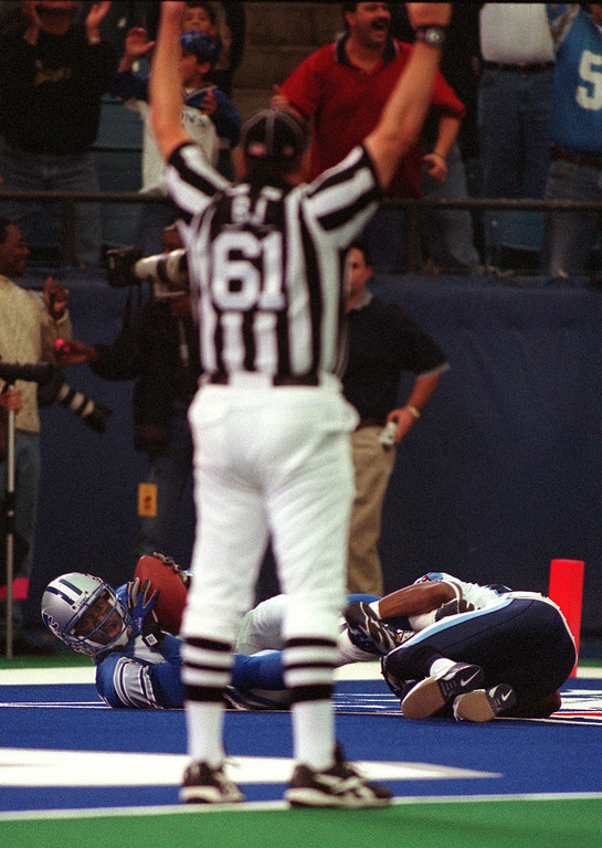 . Detroit Lions wide receiver  Germane Crowell (left)  hits the turf in the endzone with Tennessee Titan cornerback Andre Dyson  at his feet as Back Judge Keith Ferguson  signals a touchdown in the Lions 27-24 loss at the Pontiac Silverdome Sunday.  Crowell later injured his knee tendon and likely will be out the season.