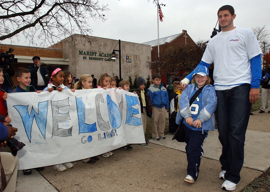 . Sydney Newby, second grade, is greeted by fellow students as she arrives at school with Detroit Lions QB Dan Orlovsky at Notre Dame Marist Academy in Waterford Twp.