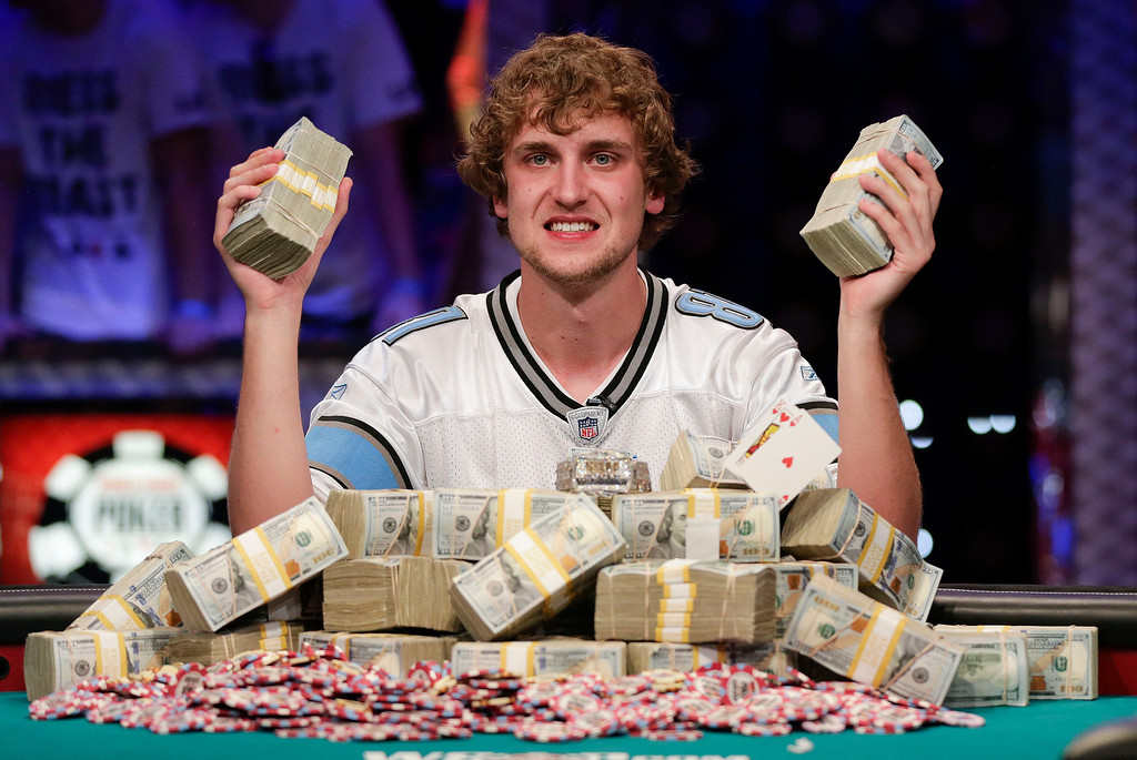. Ryan Riess holds up two bricks of $100 bills after winning the World Series of Poker Final Table, Tuesday, Nov. 5, 2013, in Las Vegas. Riess defeated runner up Jay Farber for an $8.4 million payout (AP Photo/Julie Jacobson)
