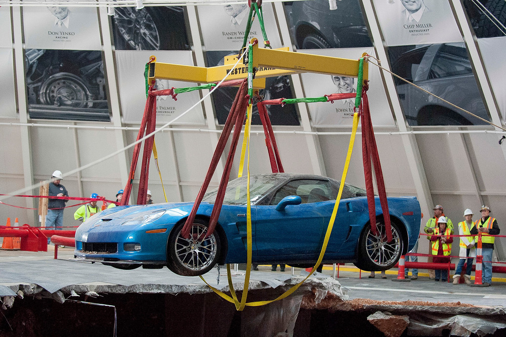 . One of eight Chevrolet Corvettes is removed from a sinkhole in the Skydome at the National Corvette Museum, Monday, March. 3, 2014, in Bowling Green, Ky.  On Feb. 12, a large sinkhole swallowed eight prized cars like they were toys, piling them in a heap amid loose dirt and concrete fragments. (AP Photo/Daily News, Alex Slitz)
