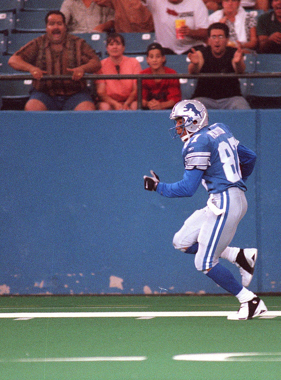 . As front row fans cheer him on, Detroit Lions Wide Receiver Johnnie Morton races up the visiting sideline for a touchdown early in the first quarter of an exhibition game against the Cincinnati Bengals at the Pontiac Silverdome Friday night.