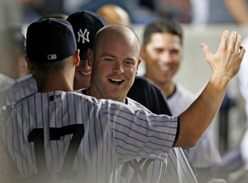 . New York Yankees Brian McCann celebrates with Yankees shortstop Brendan Ryan (17) after hitting a seventh-inning, go-ahead, solo home run off Detroit Tigers starting pitcher Justin Verlander in the Yankees 5-1 victory over the Tigers in a baseball game at Yankee Stadium in New York, Wednesday, Aug. 6, 2014.  (AP Photo/Kathy Willens)