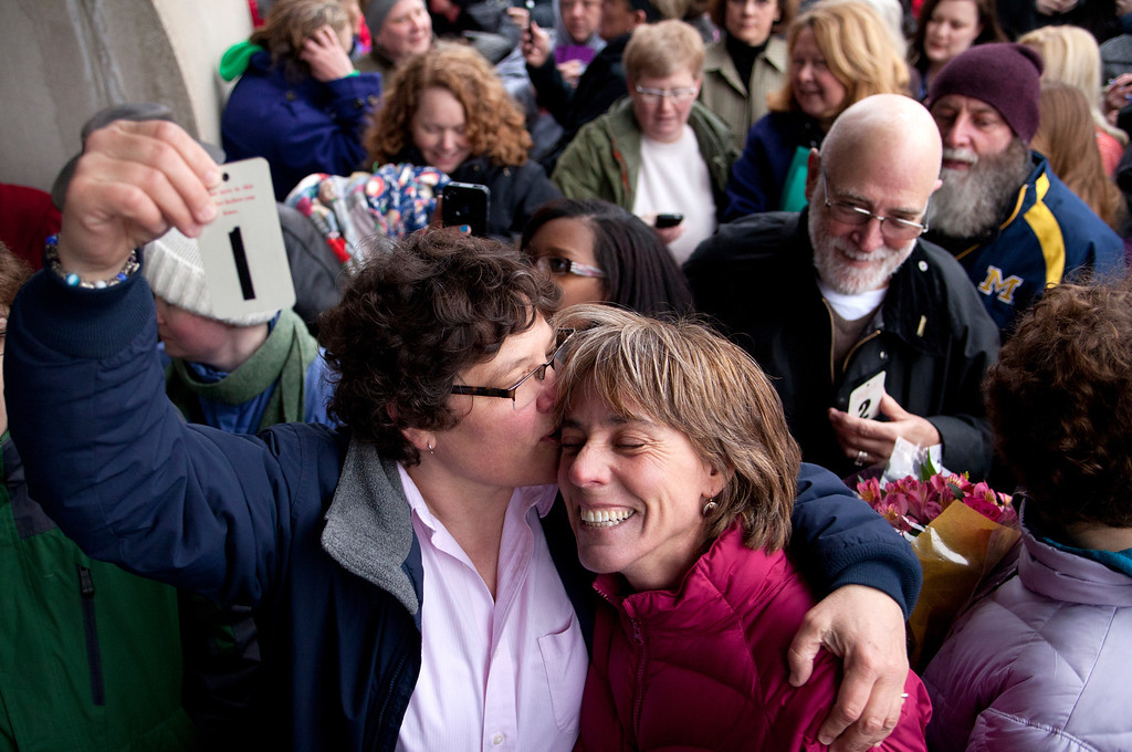 . Elizabeth Patten, left, holds up the first marriage ticket to marry her partner Johnnie Terry in front of the Washtenaw County Clerks office in Ann Arbor, Mich., on Saturday, March 22, 2014.  A federal judge has struck down Michigan\'s ban on gay marriage Friday the latest in a series of decisions overturning similar laws across the U.S. Some counties plan to issue marriage licenses to same-sex couples Saturday, less than 24 hours after a judge overturned Michigan\'s ban on gay marriage. (AP Photo/The Ann Arbor News, Patrick Record)