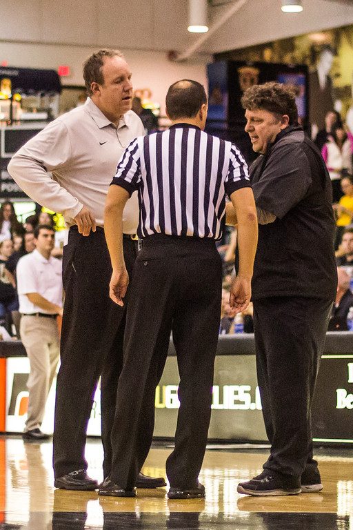 . Oakland head coach Greg Kampe (right) and assistant coach Darren Sorenson (left) discuss matters with an official Tuesday, Oct. 29, 2013 at the Athletics Center O\'rena. Photo by Dylan Dulberg