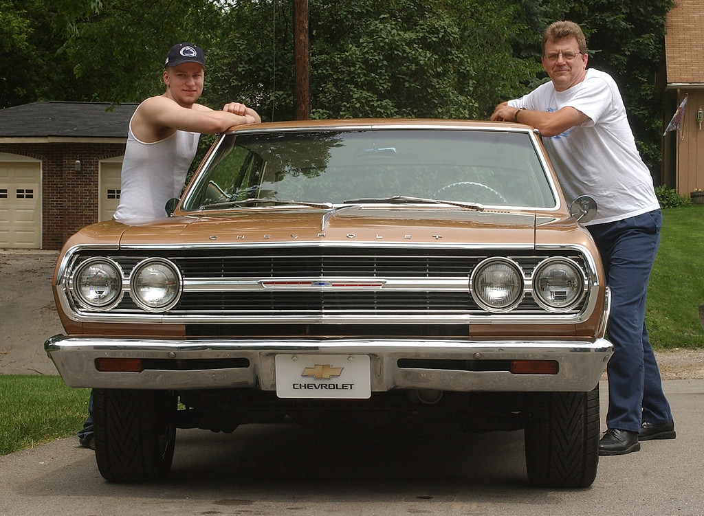 . (f.left) Riley and Kent Woiak, of Lake Orion, with a 1965 Chevrolet Chevelle Malibu they restored and will be driving in this year\'s Woodward Dream Cruise, Monday June 14, 2004.